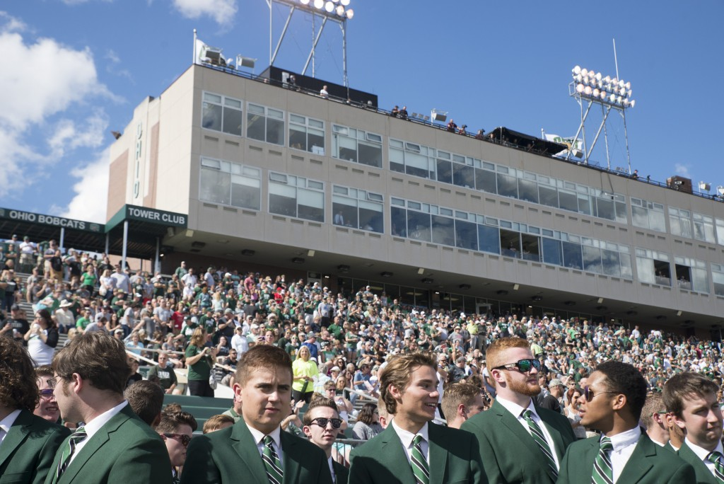 Members of the Singing Men of Ohio interact with each other on the sidelines of Peden Stadium before Ohio University's homecoming football game against Central Michigan on Saturday. (Austin Janning/WOUB)