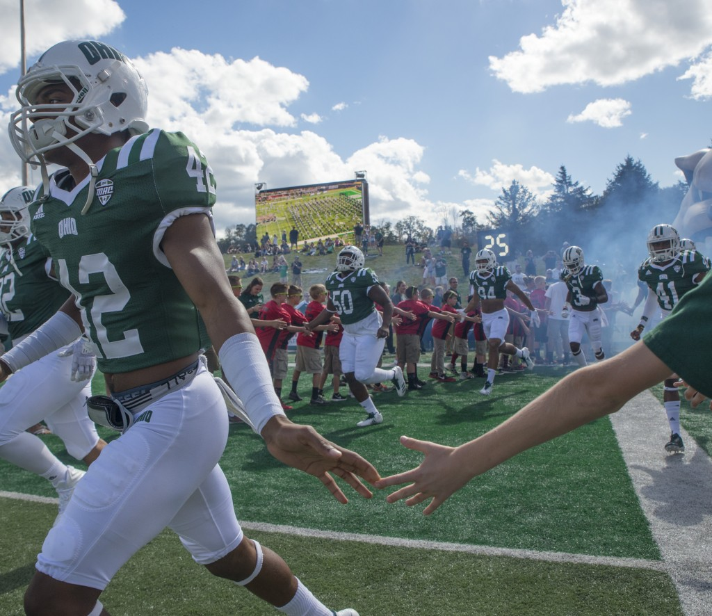 Ohio cornerback Xavior Motley gives a high-five with a young fan during Ohio University's homecoming football game against Central Michigan on Saturday. (Austin Janning/WOUB)