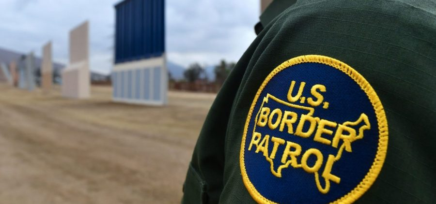 A U.S. Border Patrol officer stands near prototypes of President Trump's proposed border wall in San Diego.