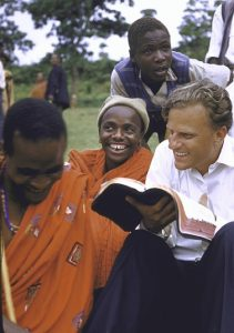 Graham traveled all over the world, spreading the Gospel. Here, he shows his Bible to Waarusha warriors near Mount Meruin in what is now Tanzania.