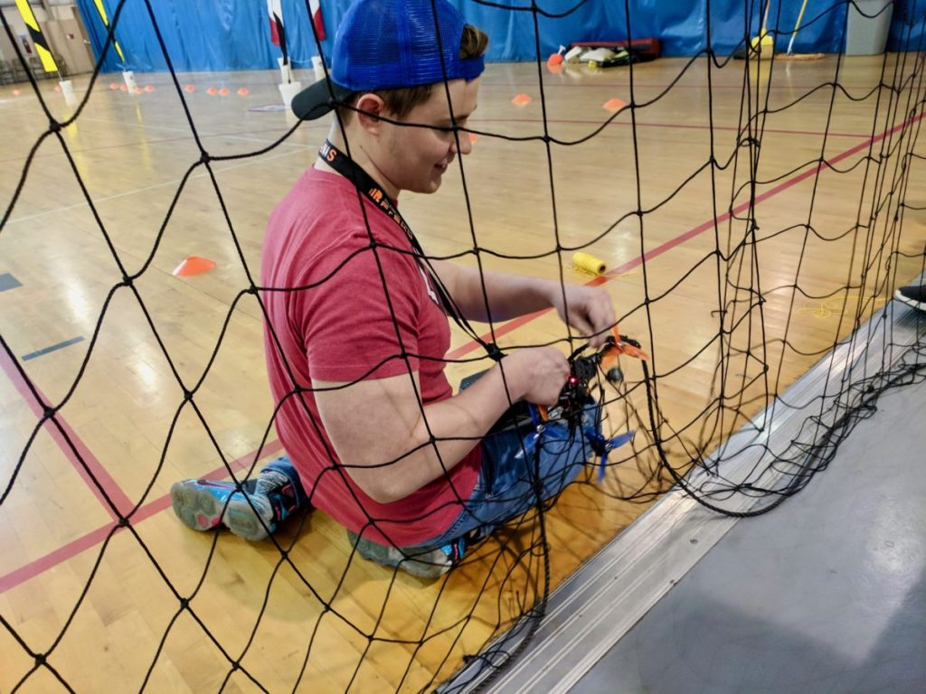 Franklin Combs untangling drone from netting