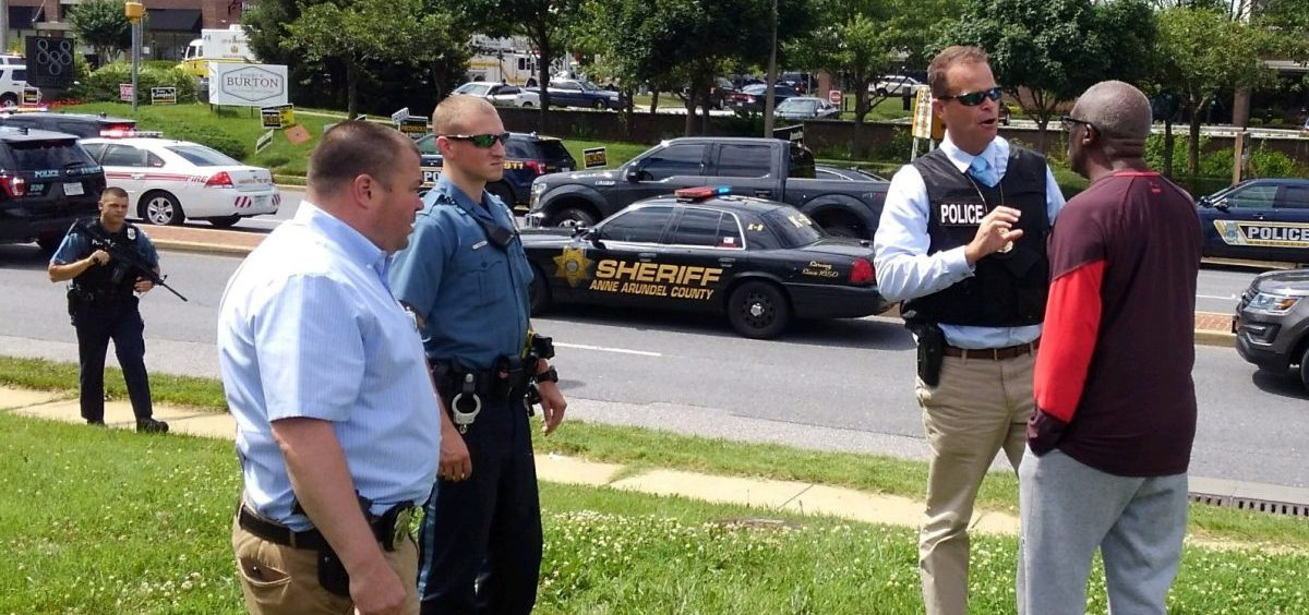 Police officers talk to a man as they respond to an active shooter at Maryland's Capital Gazette newspaper in Annapolis on Thursday.