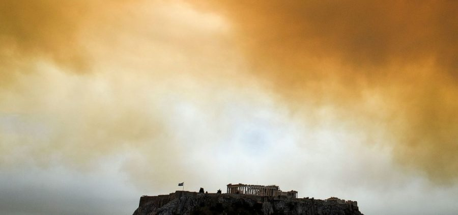 A picture taken on July 23, 2018 shows the Parthenon temple on the Acropolis hill in Athens as smoke billows in background during a wildfire in Kineta, near Athens.