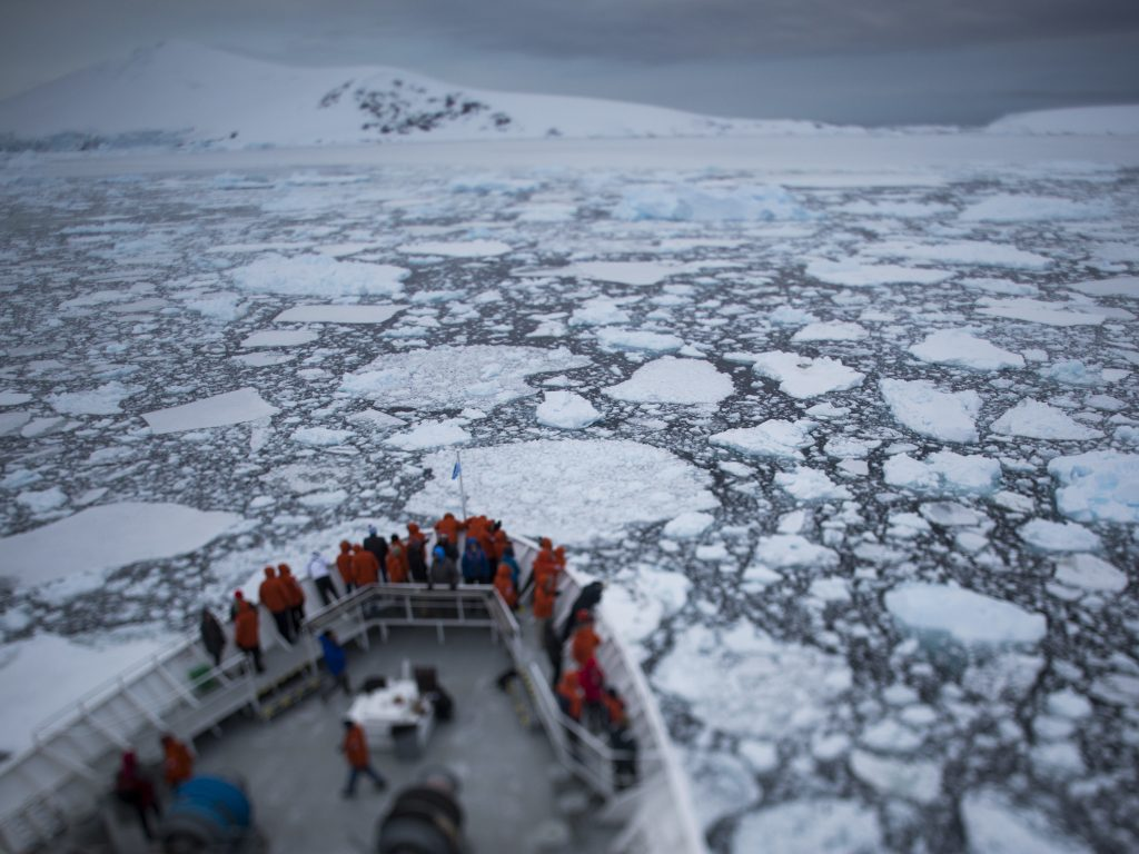 Passengers on the National Geographic Explorer gather to watch as the ship navigates through pieces of sea ice in the Antarctic Peninsula's Lemaire Channel.