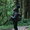 """Matt Mikkelsen carries """"Fritz,"""" his microphone system, to the path in the Hoh Rain Forest that leads to One Square Inch of Silence in Washington's Olympic National Park."""