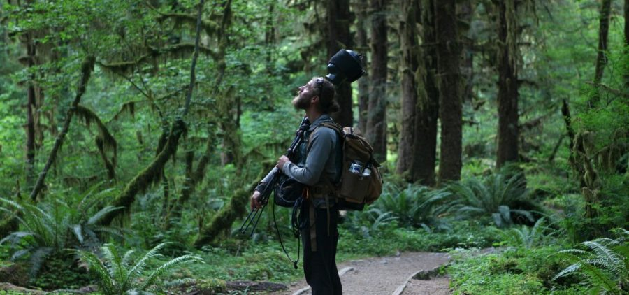 "Matt Mikkelsen carries ""Fritz,"" his microphone system, to the path in the Hoh Rain Forest that leads to One Square Inch of Silence in Washington's Olympic National Park."