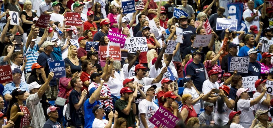 "Signs bearing the letter ""Q"" are visible at President Trump's campaign rally in Florida on Tuesday. They're related to the ""QAnon"" conspiracy theory."