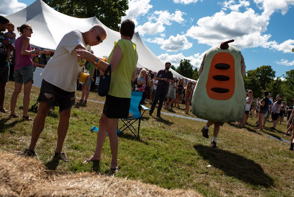 A pawpaw mascot dances its way to the main stage as festival-goers watch on Saturday, September 18, 2018. (Nickolas Oatley/WOUB)