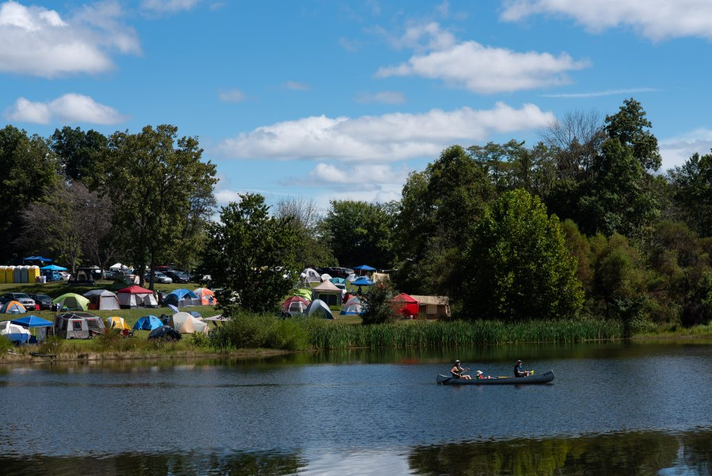 A family kayaks in front of Pawpaw Festival tents on Lake Snowden. (Nickolas Oatley/WOUB)