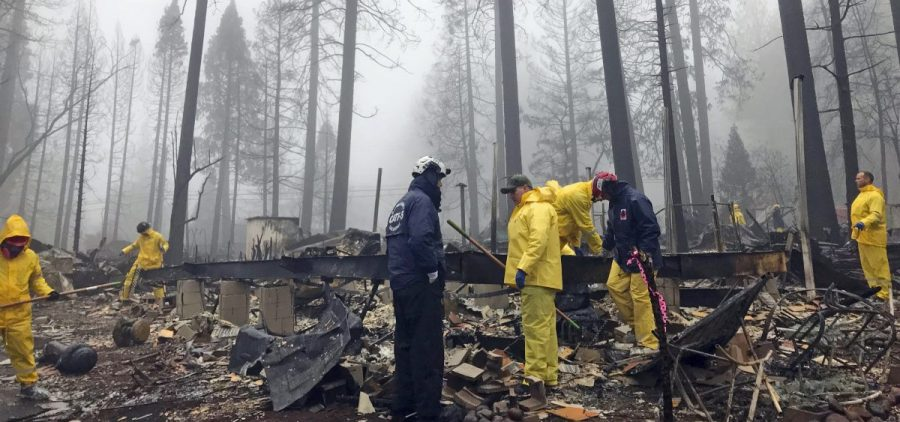 Volunteers search a mobile home park in Paradise, Calif. Government scientists predict wildfires like the one that struck this community will contribute to billions in loses for the U.S. economy.