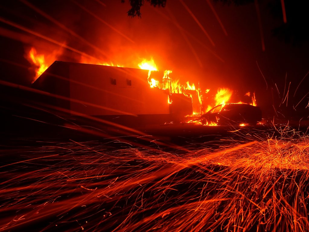 Embers blow on the wind as the Camp Fire blazes its way through Paradise, Calif., on Thursday.