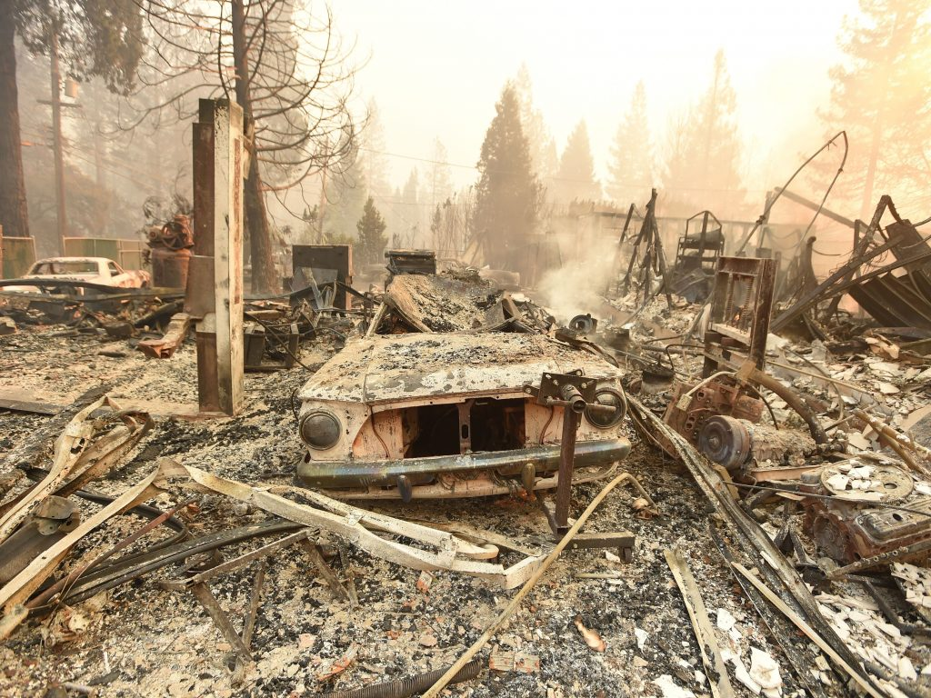The charred remains of a vehicle and home are seen during the Camp Fire in Paradise, Calif., on Thursday.