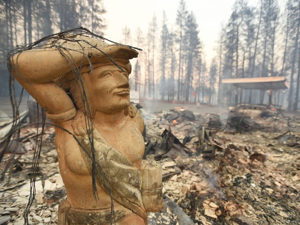 A statue stands amid the rubble of a smoldering property Thursday in Paradise, Calif., which was ravaged by the Camp Fire.