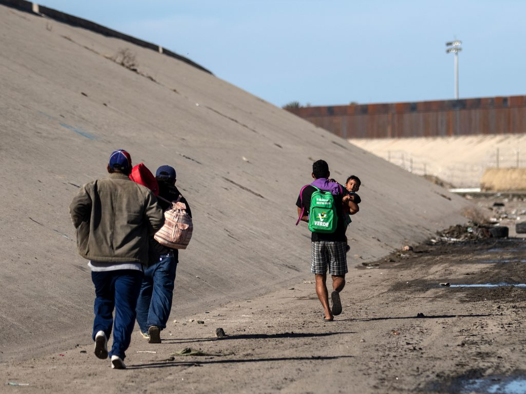 Central American migrants run along the shallow concrete waterway of the Tijuana River.