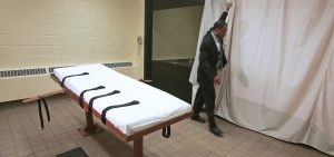 In this November 2005 file photo, Larry Greene, public information director of the Southern Ohio Correctional Facility, demonstrates how a curtain is pulled between the death chamber and witness room at the prison in Lucasville, Ohio.