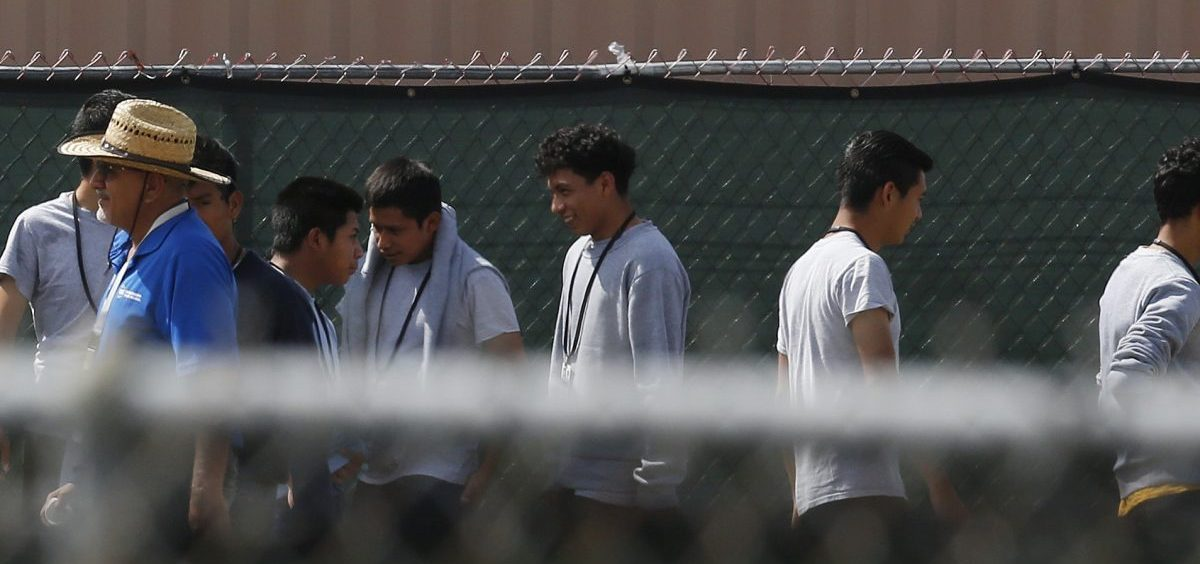Migrant children walk outside the Homestead Temporary Shelter for Unaccompanied Children in Homestead, Fla. Shelters for migrant children are almost at capacity and the federal government says they will now speed the release of thousands before Christmas.