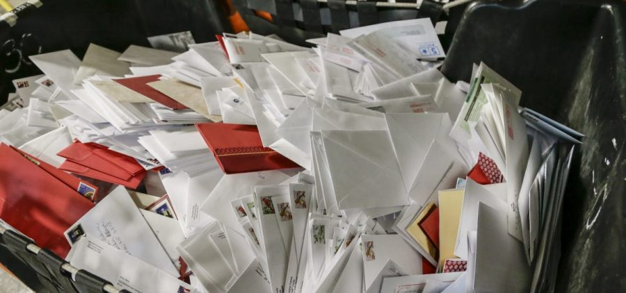 Letters wait in bins for sorting at the main post office in Omaha, Neb. The price of a Forever Stamp has increased 10 percent as the U.S. Postal Service contends with billions of dollars in annual losses.