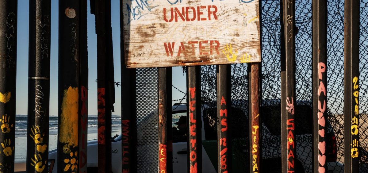 A Border Patrol officer inside his vehicle guards the border fence at San Diego across the border from Tijuana, Mexico.