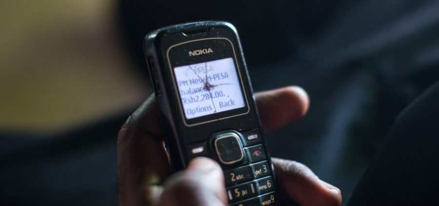 A poor resident of a village in Kenya checks his phone to confirm that a cash transfer has been made.