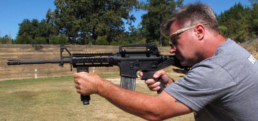 "Shooting instructor Frankie McRae aims an AR-15 rifle fitted with a ""bump stock"" that allows the semi-automatic to shoot as fast as an illegal machine gun. As of March 26, bump stocks will be effectively illegal to own unless a court puts an injunction on the federal ban."