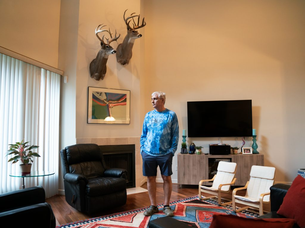 John Papadopoulos stands in the rental home in Houston where he and his family moved after their house flooded. The taxidermied deer are among the few items they were able to rescue from their flooded home.
