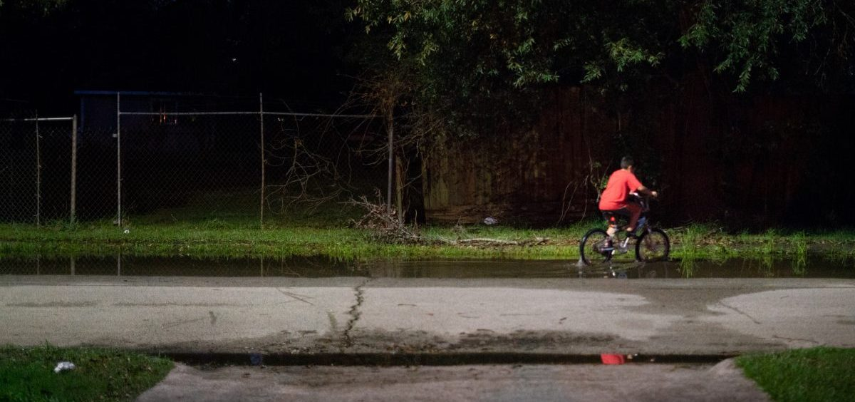 A boy rides his bike through still water after a thunderstorm in the Lakewood area of East Houston, which flooded during Hurricane Harvey.