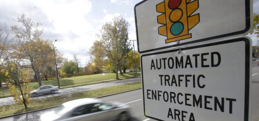 Motorists drive past a sign warning of upcoming traffic cameras in Cleveland.
