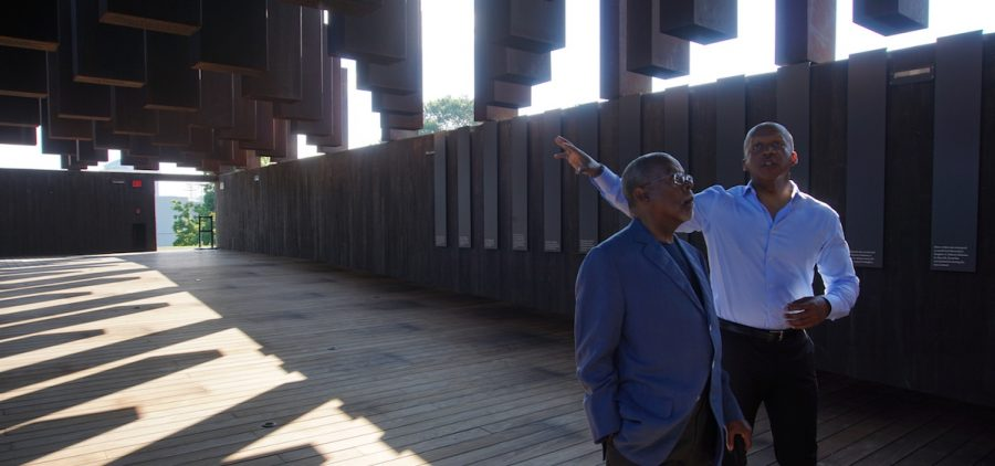 Henry Louis Gates, Jr., executive producer and host of Reconstruction: America After the Civil War, and Bryan Stevenson, founder and executive director of the Equal Justice Initiative, walk through the National Memorial for Peace and Justice in Montgomery, AL.