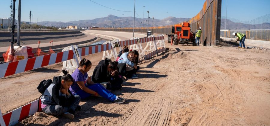 Salvadoran migrants wait for transportation after turning themselves in to U.S. Border Patrol agents in El Paso, Texas — where a border fence is under construction. The Pentagon says it will spend up to $1 billion to help build the fence.