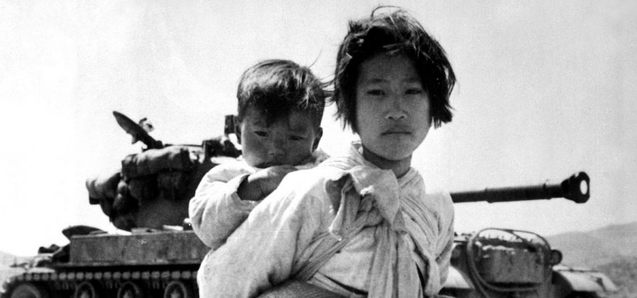 With her brother on her back a war weary Korean girl tiredly trudges by a stalled M-26 tank, at Haengju, Korea, 6/9/51.