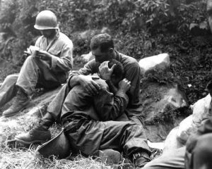 A grief stricken American infantryman whose buddy has been killed in action is comforted by another soldier