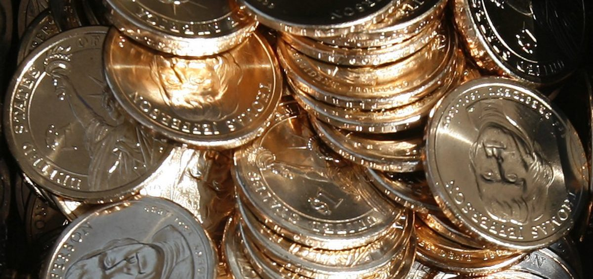 A pile of newly minted one-dollar coins honoring former Thomas Jefferson are seen at the unveiling by the U.S. Mint in Washington, D.C., in 2007. In a turnaround, congressional analysts are no longer recommending a phaseout of paper dollars in favor a dollar coin.