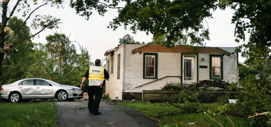 Storm damage litters a residential neighborhood, in Dayton, Ohio, Tuesday, after a rapid-fire line of apparent tornadoes tore across Indiana and Ohio overnight. The storms were packed so closely together that one crossed the path carved by another.