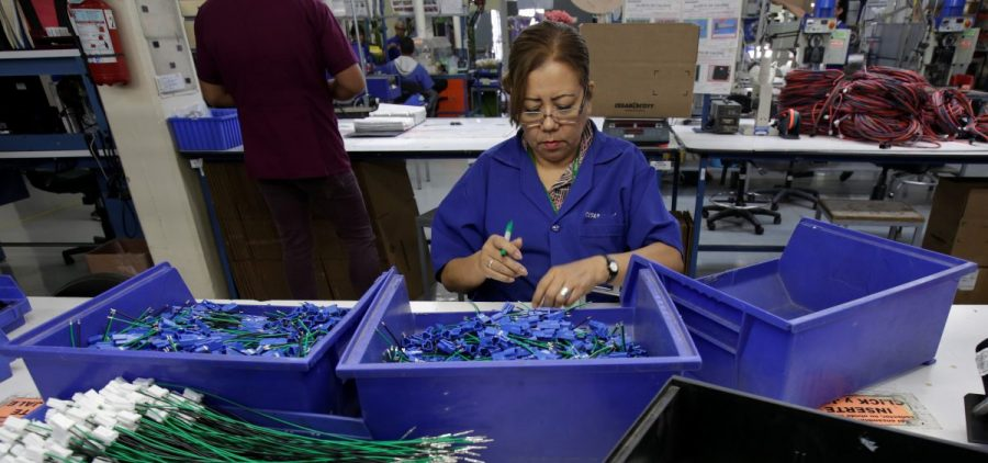 An employee works at a wiring harness and cable assembly manufacturing company in Ciudad Juárez, Mexico, that exports to the U.S. in 2017. The auto industry says threatened tariffs would play havoc with supply chains.
