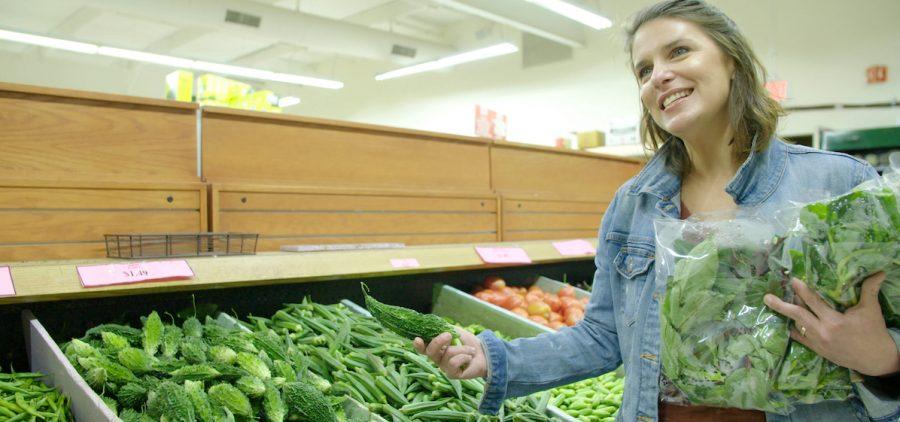 Vivian Howard looking a produce at a market