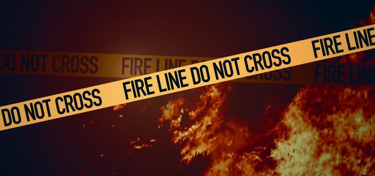 Fire line tape with flames in the background