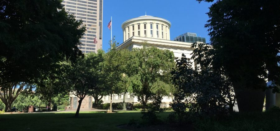 The Ohio Statehouse behind trees