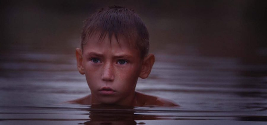 young boy swimming in pond in water up to his neck