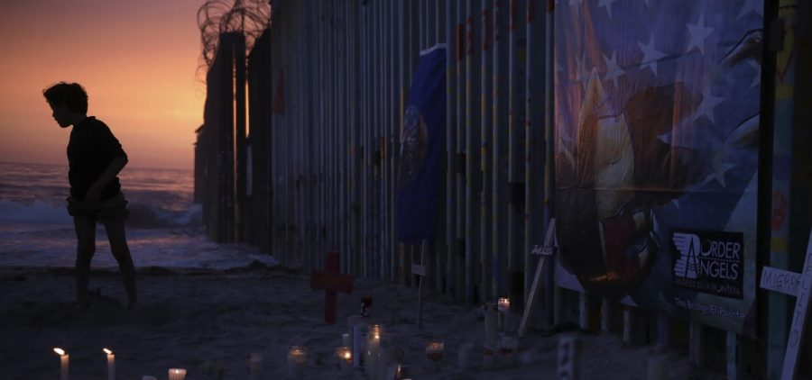 A youth in Tijuana, Mexico, stands by the border fence that separates Mexico from the United States, where candles and crosses stand in memory of migrants who have died during their journey toward the U.S.
