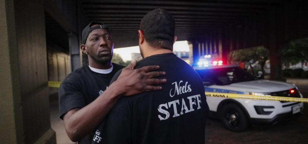 Witnesses comfort one another at the scene of a mass shooting, Sunday, Aug. 4, 2019, in Dayton, Ohio. Several people in Ohio have been killed in the second mass shooting in the U.S. in less than 24 hours, and the suspected shooter is also deceased, police said. (AP Photo| John Minchillo)