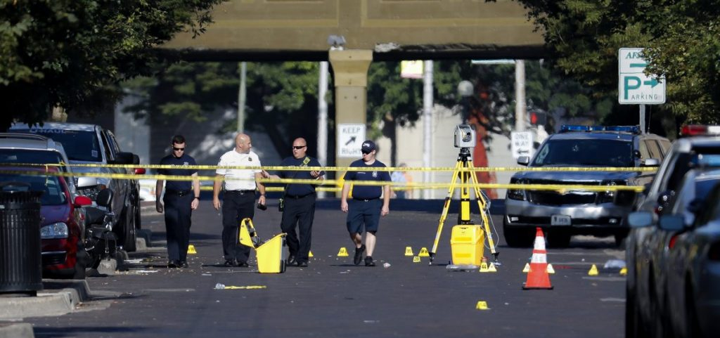 Authorities walk among evidence markers at the scene of a mass shooting, Sunday, Aug. 4, 2019, in Dayton, Ohio. Severral people in Ohio have been killed in the second mass shooting in the U.S. in less than 24 hours, and the suspected shooter is also deceased, police said. (AP Photo | John Minchillo)