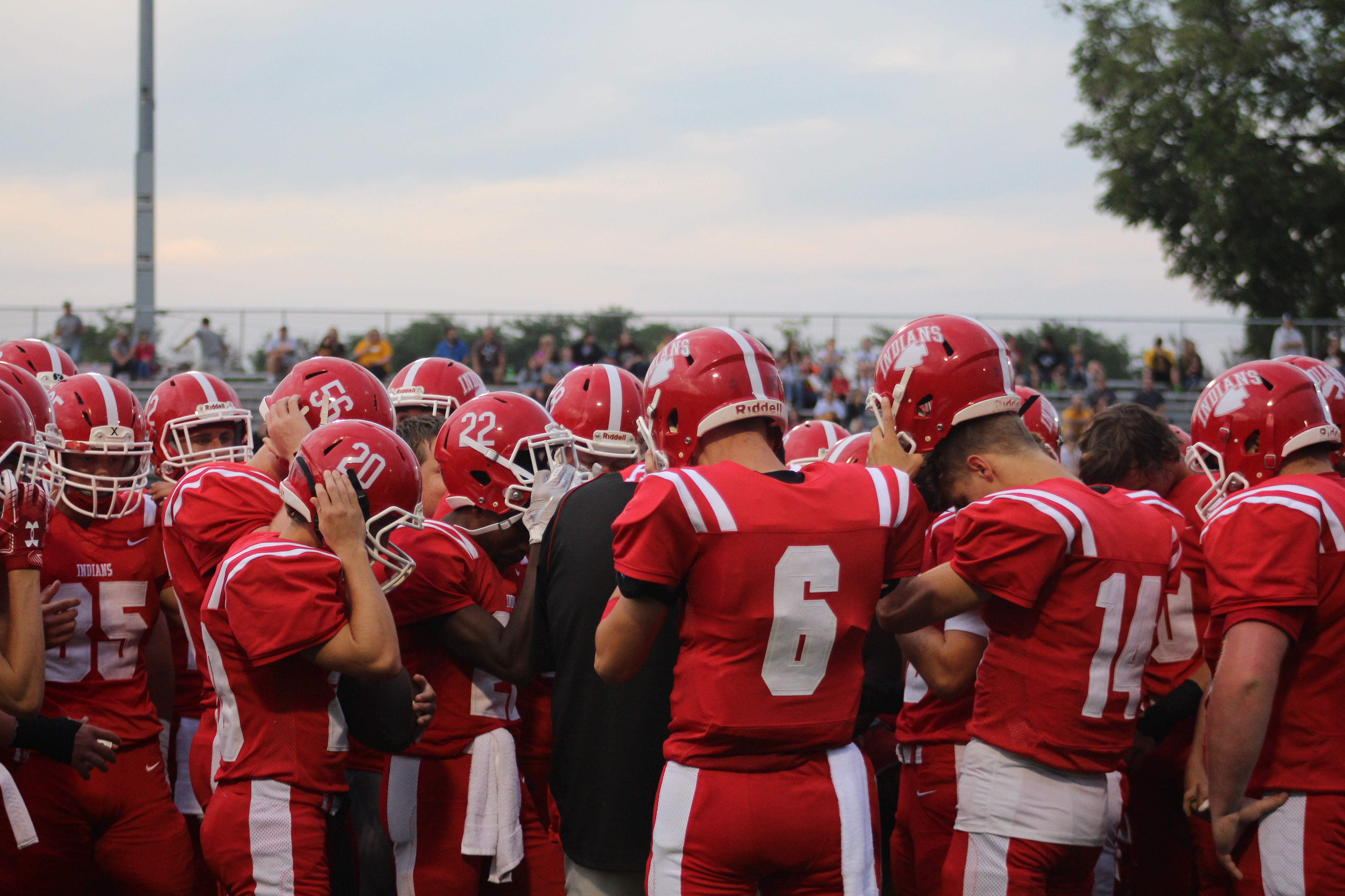 Hillsboro players remove their helmets in the huddle