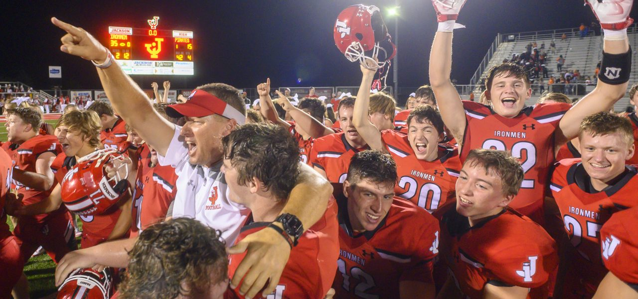 Head coach Andy Hall and his team celebrate after a win against Wheelersburg on Sept. 27, 2019.