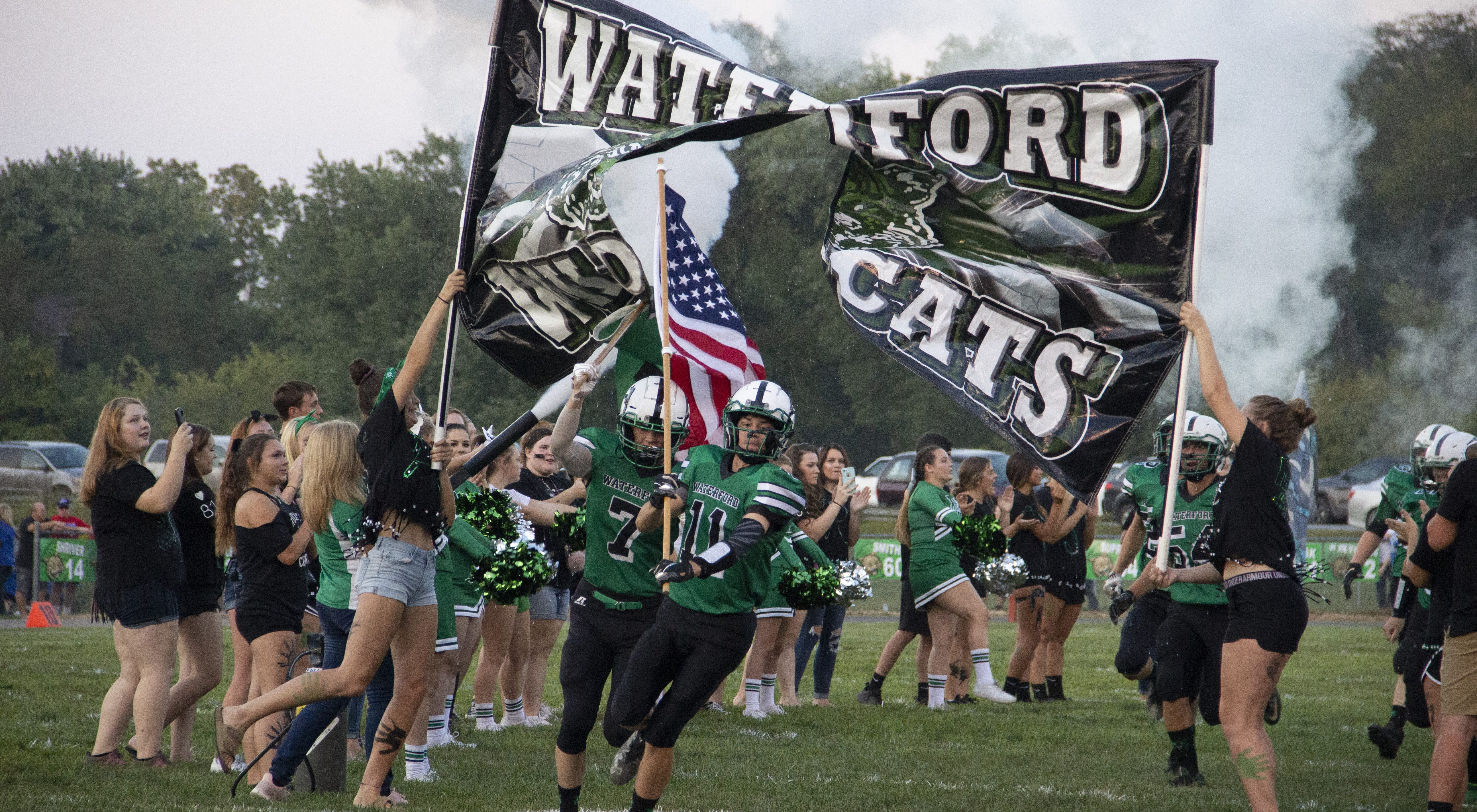 The Waterford Wildcats break through the banner