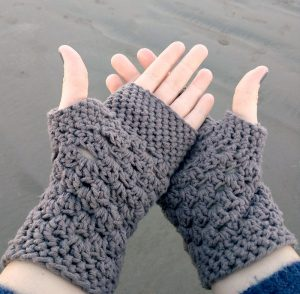 Two hands display gloves made using crochet techniques