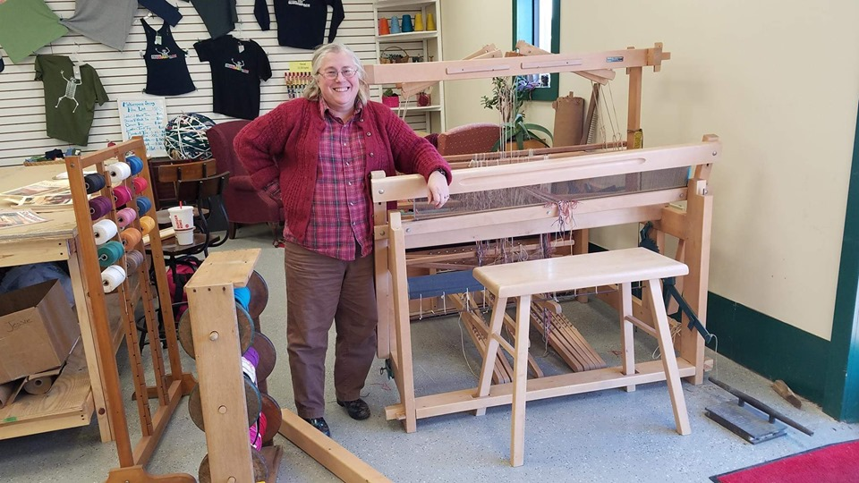 A man stands next to a weaving machine