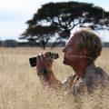 man with binoculars in the Serengeti grasslands