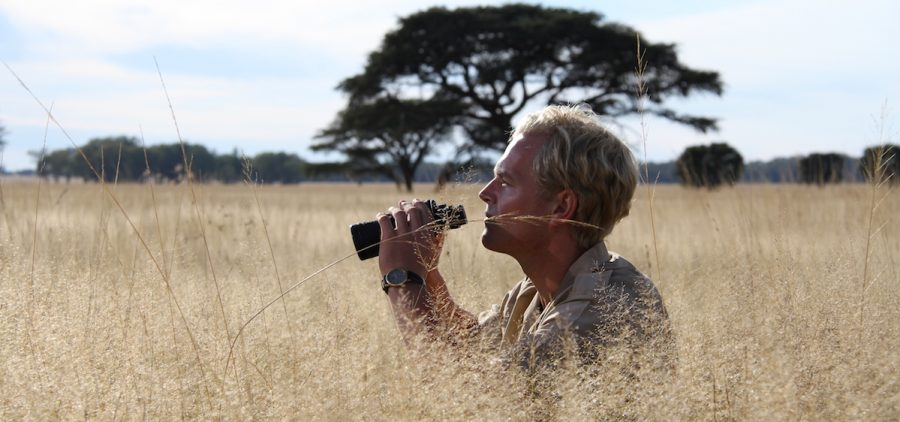 man with binoculars in the Serengeti grasslands