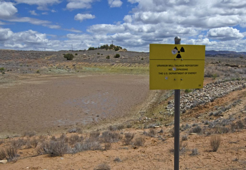 Bullet holes pockmark a sign showing the location of buried uranium mill waste in southwest Colorado.