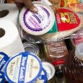 A food pantry client adds a carton of yogurt to her cart at the food pantry at Jewish Family Services in Denver, Colo.